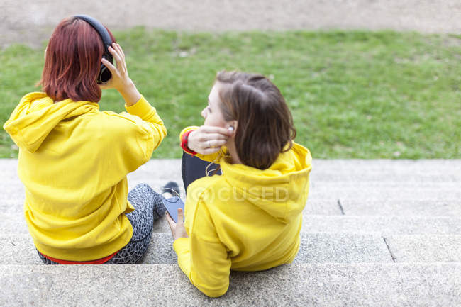 Young women with earphones resting on steps — Stock Photo