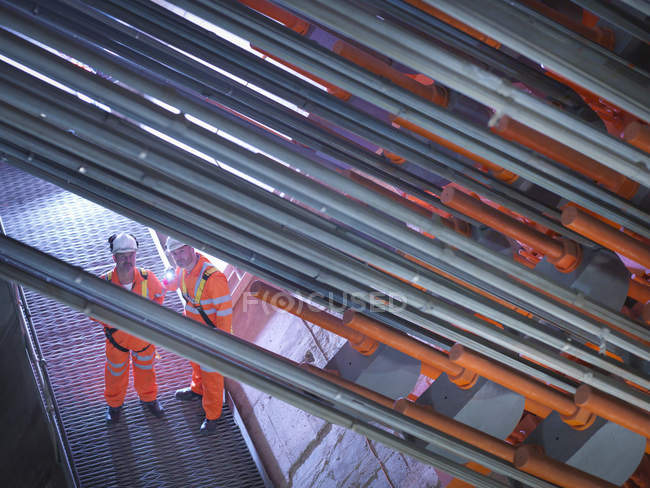 Civil engineers using torch to inspecting cable anchorage in suspension bridge, East Yorkshire, United Kingdom — Stock Photo