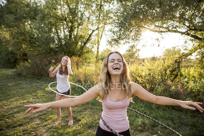 Два молодих дівчат у сільській місцевості, валяти дурня, використовуючи Хула обручі, — стокове фото