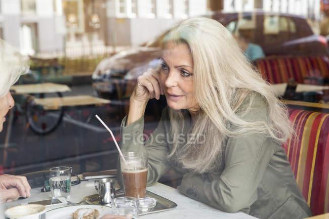 Madre e figlia che si siedono insieme nel café, visto attraverso la finestra di café — Foto stock