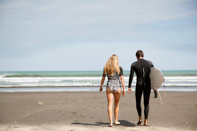 Giovane coppia che cammina verso il mare, giovane che porta la tavola da surf — Foto stock