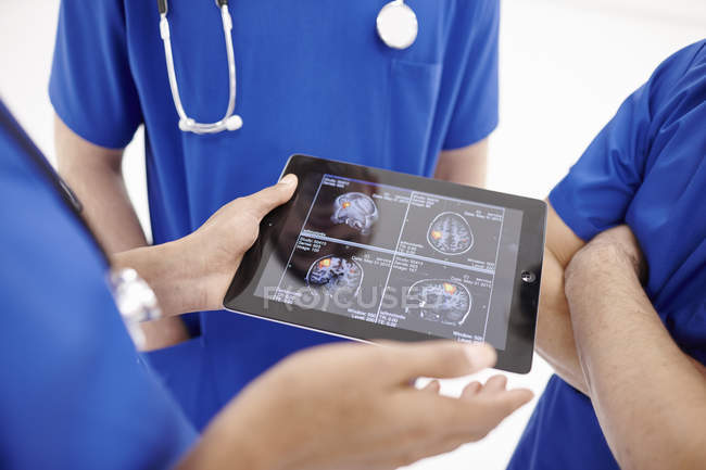 Doctors looking at scans on digital tablet — Stock Photo