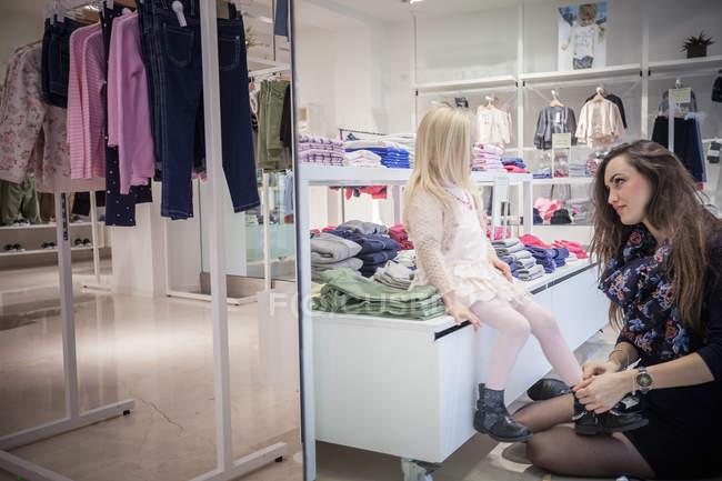 Мати намагається взуття на дочку в магазині одягу дитячий — стокове фото