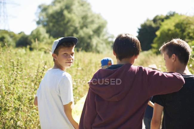 Portrait of little boy wearing cap with friends — Stock Photo
