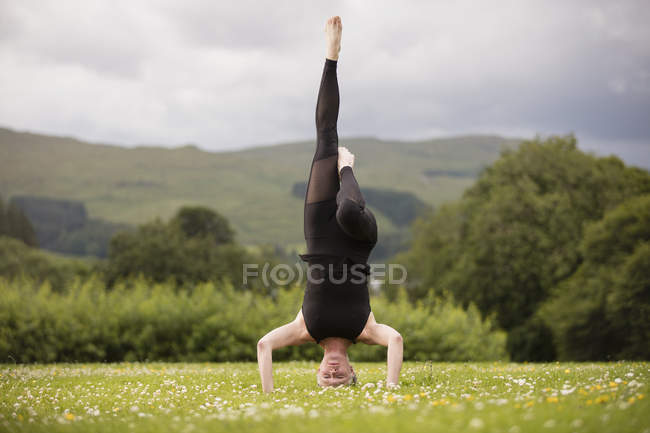 Mature woman practicing yoga standing on head with leg raised in field — Stock Photo