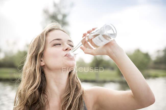 Молодая женщина пьет воду из бутылки, на открытом воздухе — стоковое фото