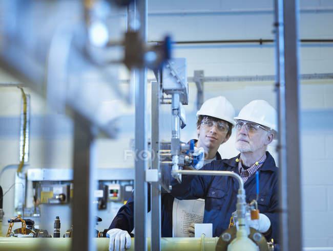 Старші та інженери, що працюють на електростанції. — стокове фото