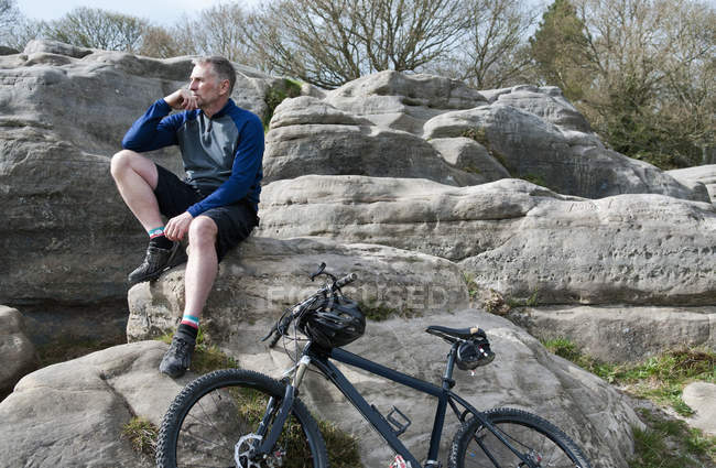 Mature male mountain sitting on rock formation — Stock Photo
