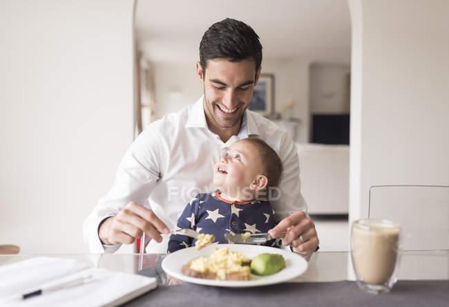 Отец и малыш едят еду. — стоковое фото