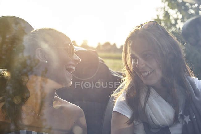 Two young female friends chatting in convertible car — Stock Photo