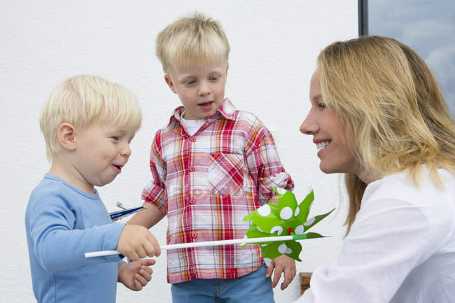 Mother and two young sons playing with pinwheel on patio — Stock Photo