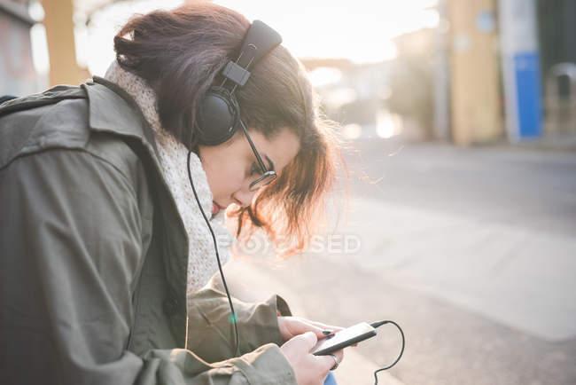 Молодая женщина, сидящая на тротуаре и читающая смс на смартфоне — стоковое фото