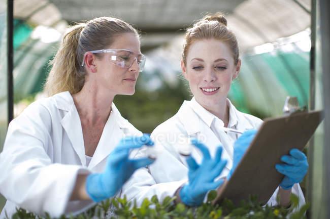 Scientifiques féminines surveillant les échantillons végétaux et enregistrant les données — Photo de stock
