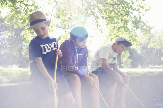 Boys holding fishing nets in sunlight — Stock Photo