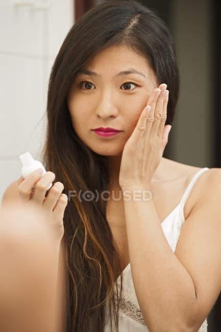 Mid adult woman applying face cream — Stock Photo