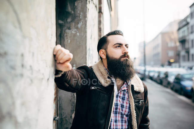 Young bearded man by concrete wall — Stock Photo