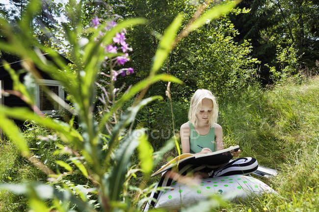 Jeune fille assise dans un environnement rural avec carnet de croquis — Photo de stock