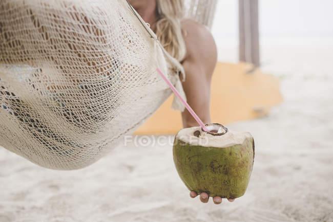 Man enjoying coconut water in hammock on beach — Stock Photo