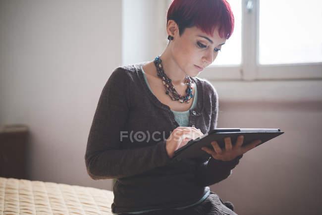 Jeune femme à la maison en utilisant une tablette numérique — Photo de stock