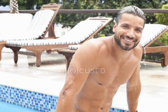 Людина сидить на стільці біля басейну і дивлячись на камеру — стокове фото