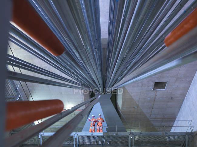Ingenieros civiles inspeccionan anclaje de cables en puente colgante, vista de bajo ángulo, East Yorkshire, Reino Unido - foto de stock