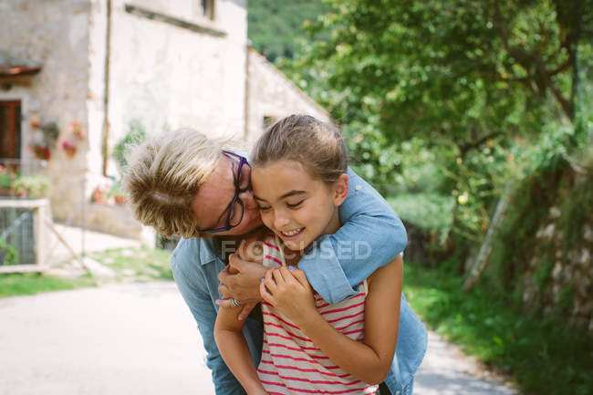 Grandmother kissing granddaughter on cheek — Stock Photo