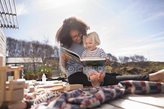 Мать читает книгу сыну на одеяле для пикника — стоковое фото