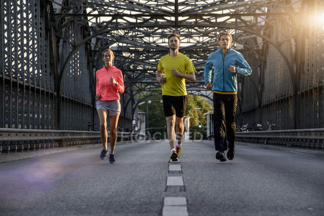 Друзья бегают по мосту, Мюнхен, Бавария, Германия — стоковое фото