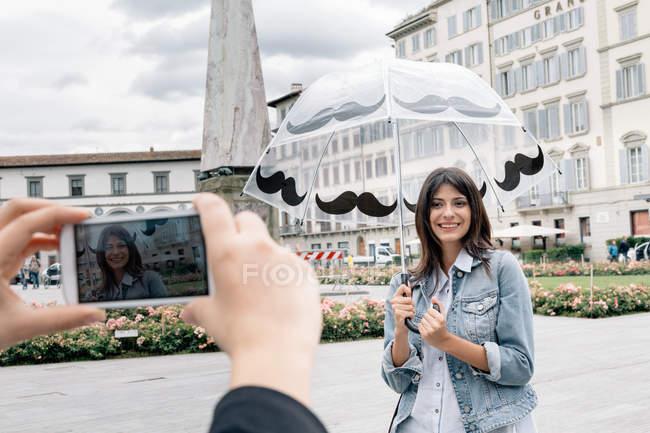 Jovem mulher segurando guarda-chuva posando para amigo usando smartphone para tirar fotos, Piazza Santa Maria Novella, Florença, Toscana, Itália — Fotografia de Stock