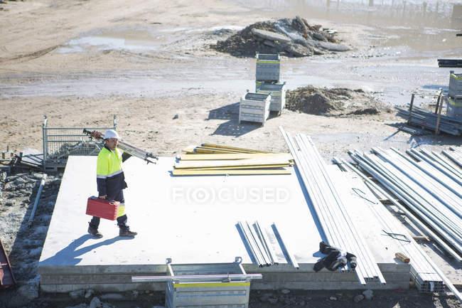 Vista de ángulo alto del maletín de transporte del topógrafo y el trípode en el sitio de construcción - foto de stock