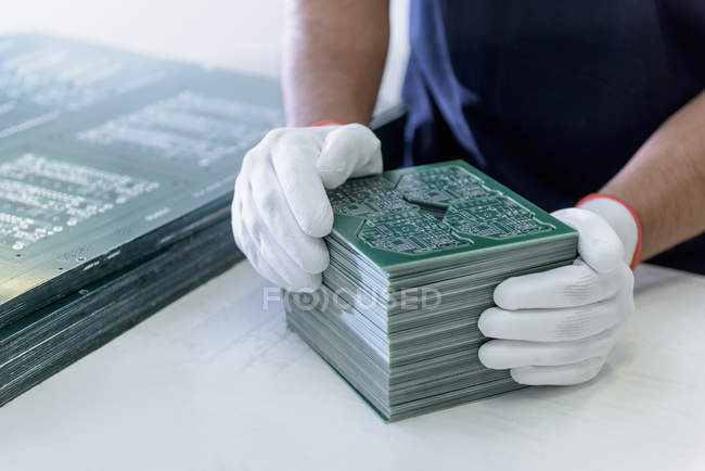 Worker arranging cut circuit boards in circuit board factory — Stock Photo