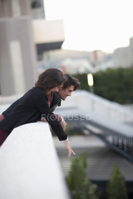 Couple looking down and pointing from city rooftop — Stock Photo