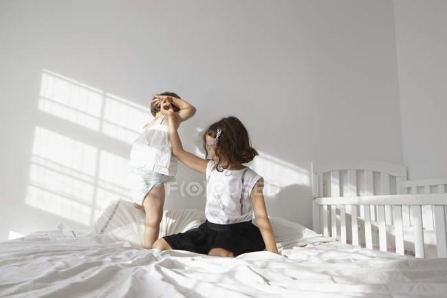 Mädchen geben helfende Hand zu weiblichen Kleinkind Schwester zu toddling auf dem Bett — Stockfoto