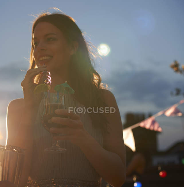 Woman holding cocktail at early evening party — Stock Photo