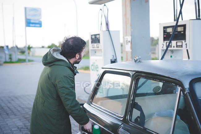 Homme à l'aide de la pompe à carburant pour voitures anciennes dans la station de remplissage de gaz — Photo de stock