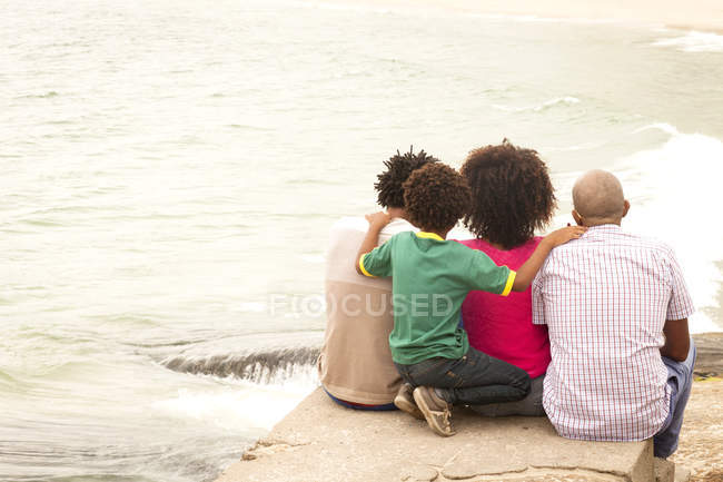 Rear view of mature man and family looking out to sea on beach — Stock Photo