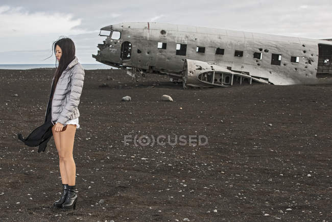Woman standing against old airplane and volcanic landscape — Stock Photo