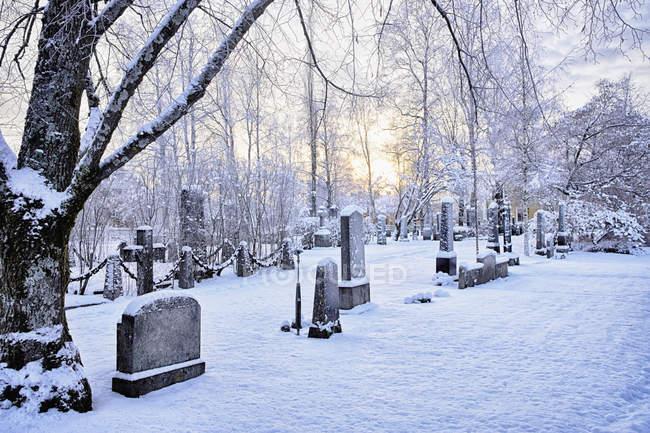 Vue des pierres tombales dans le cimetière couvert de neige au crépuscule, Hemavan, Suède — Photo de stock