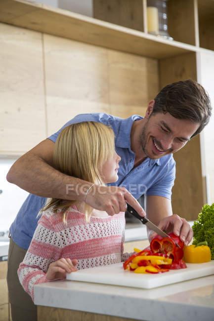 Homem ensinando filha a cortar legumes no balcão de cozinha — Fotografia de Stock