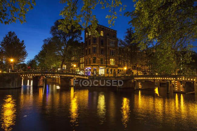 Canal waterfront and bridge at night, Amsterdam, Países Bajos - foto de stock