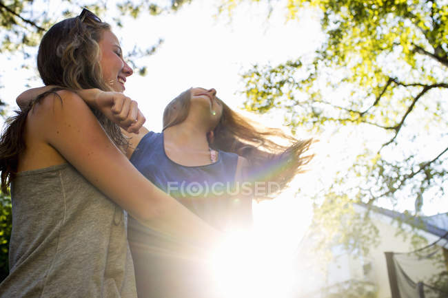 Two teenage girls dancing in sunlit park — Stock Photo