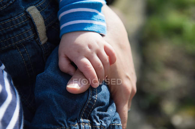 Baby boy holding mother's thumb, focus on hands — Stock Photo