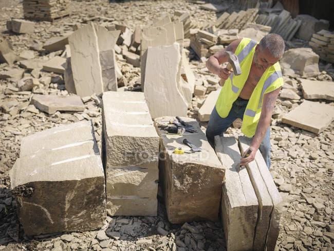 Ouvrier de carrière fendant du grès dans la carrière de pierre Yorkshire, vue surélevée — Photo de stock