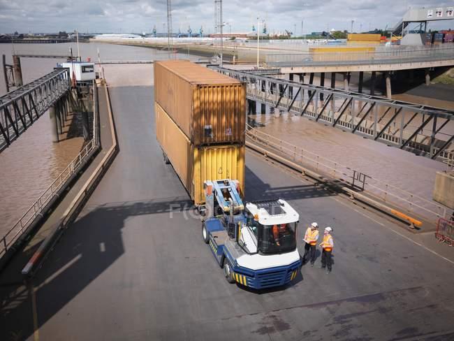 Elevated view of shipping containers and truck on ramp to ship — Stock Photo