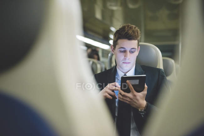 Portrait of young businessman commuter using digital tablet on train. — Stock Photo