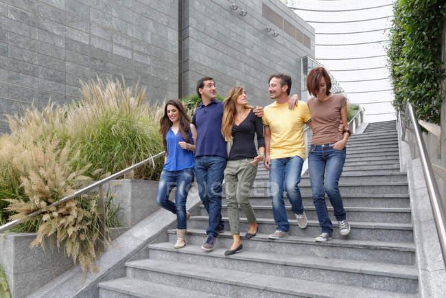 Группа друзей спускается по ступенькам вместе — стоковое фото
