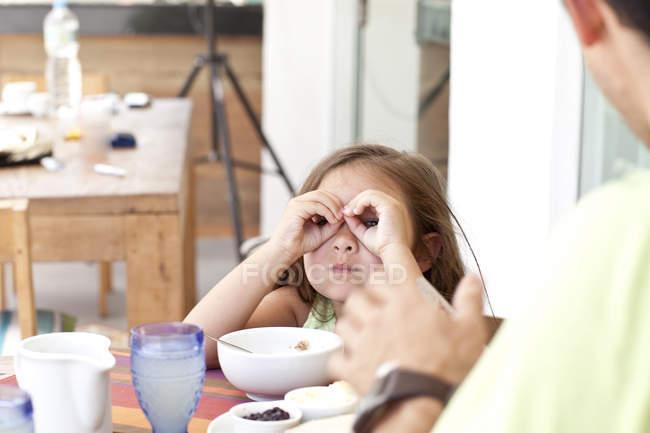 Отец и дочь сидят за завтраком, дочь делает бинокль из пальцев — стоковое фото