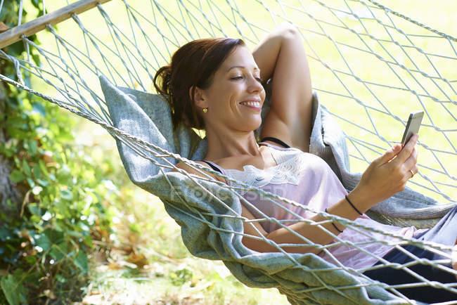 Mitte erwachsene Frau liegt in Gartenhängematte und schaut aufs Smartphone — Stockfoto