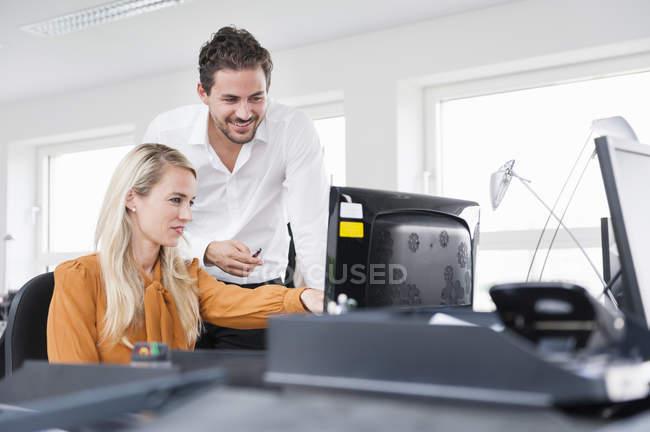 Collègues masculins et féminins utilisant l'ordinateur dans le bureau — Photo de stock
