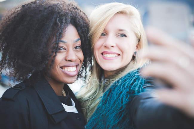 Deux jeunes femmes posant pour Smartphone selfie — Photo de stock